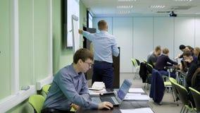 El conferenciante bien conocido conduce el entrenamiento para los encargados Hombre en el primero plano que trabaja en un ordenad