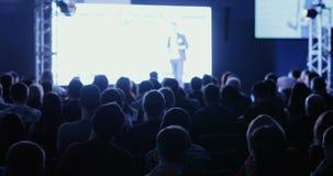 El conferenciante dice y muestra la presentación en la pantalla descriptiva a la casa llena de oyentes
