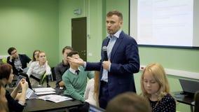 El conferenciante habla a los estudiantes en una conferencia en la economía Estudiantes en el mucho público en la universidad mod metrajes