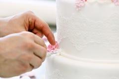 El confitero adorna el pastel de bodas blanco Imágenes de archivo libres de regalías