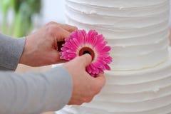 El confitero adorna el pastel de bodas blanco Fotos de archivo libres de regalías