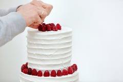 El confitero adorna el pastel de bodas blanco Imagenes de archivo