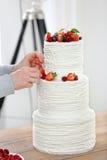 El confitero adorna el pastel de bodas blanco Imagen de archivo