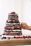 El confitero adorna el pastel de bodas desnudo rústico Fotografía de archivo
