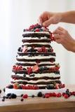 El confitero adorna el pastel de bodas desnudo rústico Fotos de archivo