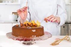 El confitero adorna la torta Fotos de archivo