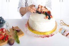 El confitero adorna la torta con la fruta Imagen de archivo libre de regalías