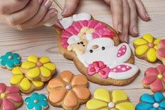 El confitero adorna las galletas en la forma de conejo Imagenes de archivo