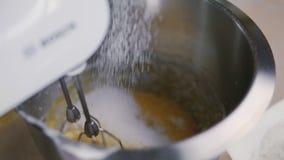 El confitero mezcla las yemas de huevo y el azúcar en un cuenco del metal Cierre de la cámara lenta para arriba almacen de metraje de vídeo