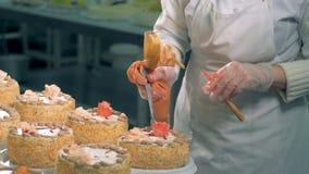 El confitero pone un cremoso subió en una torta almacen de video