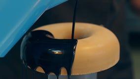 El confitero vierte el buñuelo con el chocolate líquido oscuro almacen de video