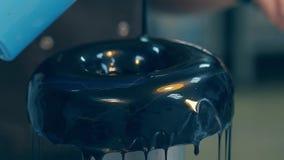 El confitero vierte capa del esmalte con brillo de la comida en el buñuelo almacen de video