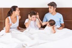 El conflicto de la familia parents la cama, niños de la pareja Imagen de archivo libre de regalías