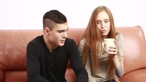 El conflicto joven hermoso de los pares que se sienta en un sofá discute infeliz Hombre joven y mujer almacen de video