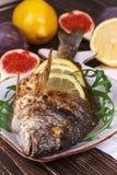 El conjunto asó a la parrilla el dorado de los pescados servido con el limón y los higos Imagen de archivo