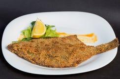El conjunto asó los pescados servidos con las hierbas, limón en la placa blanca Foto de archivo libre de regalías