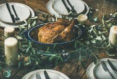 El conjunto asó el pollo para la Navidad, las placas y las velas Fotos de archivo