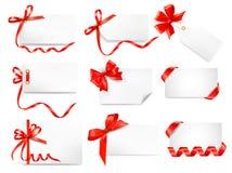 El conjunto de notas de la tarjeta con el regalo rojo arquea con las cintas Foto de archivo