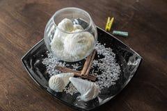 El cono de helado blanco con el coco salta en una placa negra en la tabla de madera oscura Fotografía de archivo