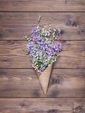 El cono de la galleta con el valle y el lilak del lirio florece en backgro de madera Imágenes de archivo libres de regalías