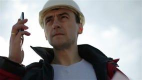 El constructor atractivo joven en un casco blanco está haciendo llamada en el teléfono móvil metrajes