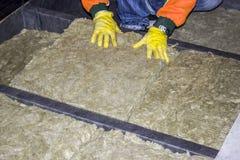 El constructor da el guante que lleva que aísla la casa de madera con lanas minerales Imagenes de archivo