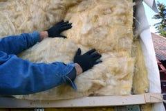 El constructor da la casa de madera aislador con lanas minerales Imagen de archivo libre de regalías