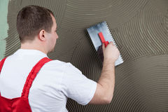 El constructor de trabajo aplica el pegamento en una pared para una baldosa cerámica f Foto de archivo libre de regalías