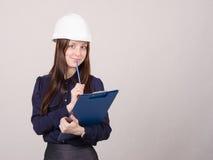 El constructor en casco escribe la carpeta del lápiz Foto de archivo libre de regalías