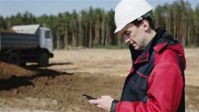 El constructor en el casco blanco está mecanografiando número en el teléfono móvil y está haciendo llamada almacen de metraje de vídeo