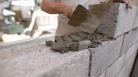 El constructor es solución imponente del edificio en una pared de bloques durante hacer la albañilería del ladrillo en un área de almacen de video