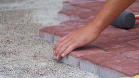 El constructor está poniendo piedras de pavimentación almacen de metraje de vídeo