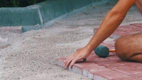 El constructor está poniendo piedras de pavimentación metrajes