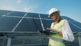 El constructor femenino está caminando a lo largo de un panel solar con un ordenador almacen de video