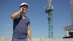 El constructor llama alguien en el teléfono almacen de metraje de vídeo
