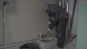 El constructor mezcla la masilla almacen de video
