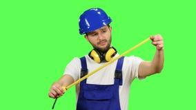 El constructor toma medidas con la ayuda de una cinta métrica Pantalla verde almacen de video