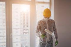 El constructor trabaja en el emplazamiento de la obra Trabajador con el rodillo del cubo y de pintura cerca de la pared imagen de archivo libre de regalías