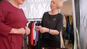 El consultor del vendedor ofrece a una mujer mayor para intentar encendido los pendientes en la tienda almacen de video