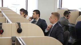 El consultor masculino del blone trabaja entre sus colegas en la oficina brillante metrajes
