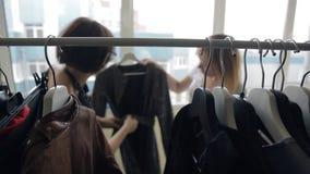 El consultor moreno muestra la capa blanco y negro rubia con la correa almacen de metraje de vídeo