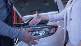 El consumidor de mujer da llaves del coche al mecánico de automóviles para la reparación y sacude las manos en la gasolinera almacen de metraje de vídeo