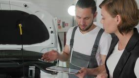 El consumidor preocupante, el mecánico de automóviles aconseja al cliente, coche roto, charla de la mujer del trabajador del serv almacen de video