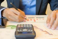 El contable calcula el informe financiero, ordenador con la carta del gráfico fotos de archivo libres de regalías