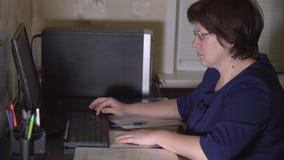El contable de mujer se está sentando en el ordenador Trabajo remoto almacen de video