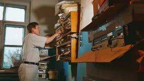 El contable del viejo hombre en una oficina vieja examina la información de papel los documentos oficina de trabajo profesional d almacen de metraje de vídeo