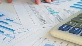El contable está comprobando resultados financieros Ciérrese para arriba de papeleo almacen de video