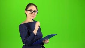 El contable registra los datos en una tableta de papel Pantalla verde almacen de video