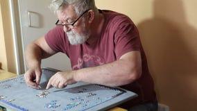 El contenido del hombre mayor que hacía una plantilla consideró rompecabezas almacen de metraje de vídeo