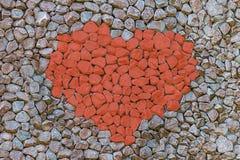 El contraste rojo de la piedra del coraz?n en un s?mbolo gris del fondo del sistema del amor de piedras pint? la base determinada fotografía de archivo